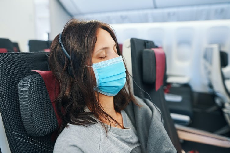 A woman sleeping on a plane, wearing headphones and a face mask.
