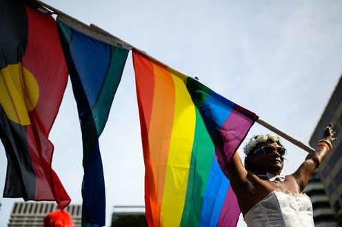 A participant waves a flag ahead of the 42nd annual Gay and Lesbian Mardi Gras parade.