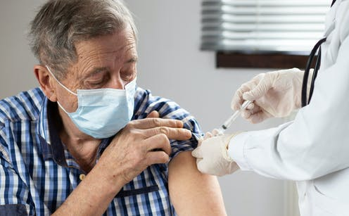 An elderly man being vaccinated