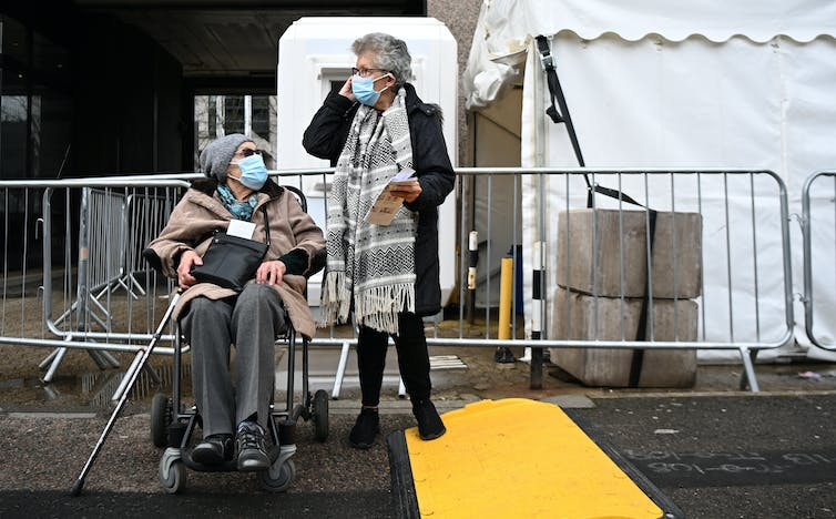 Two elderly women leaving a COVID-19 vaccination centre
