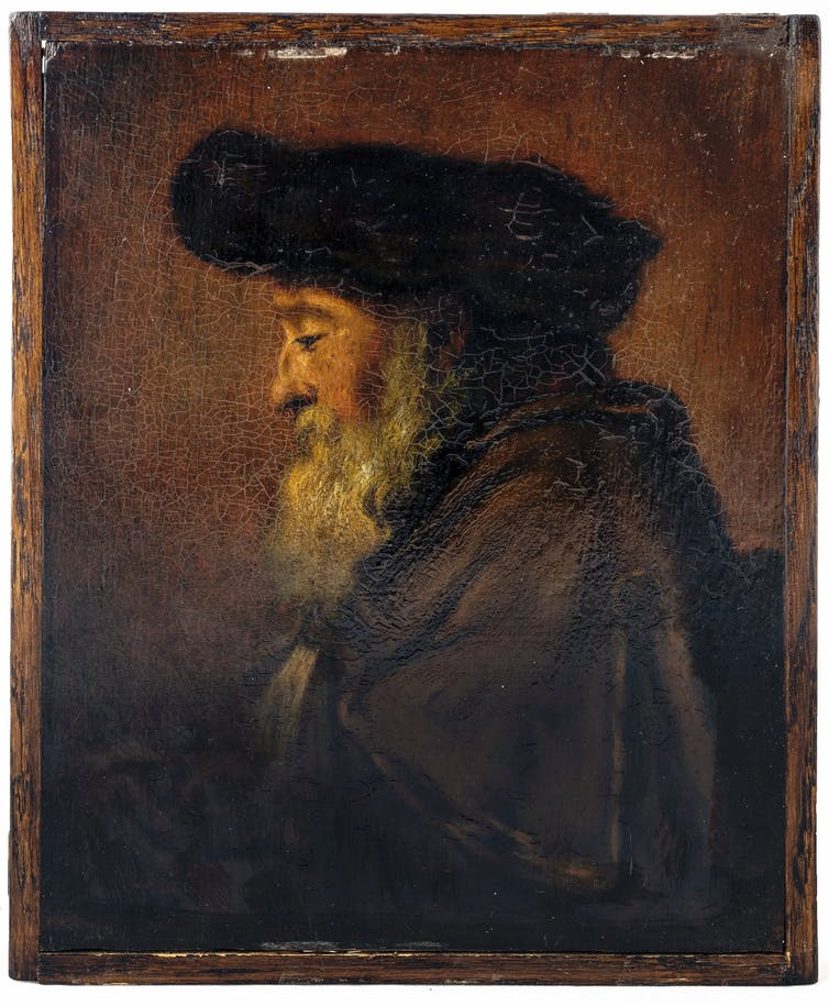 The painted profile of an elder man with a long grey beard, hat and cloak.