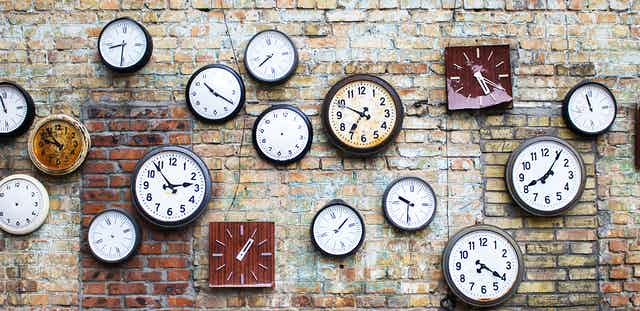 A brick wall with lots of clocks hanging up.