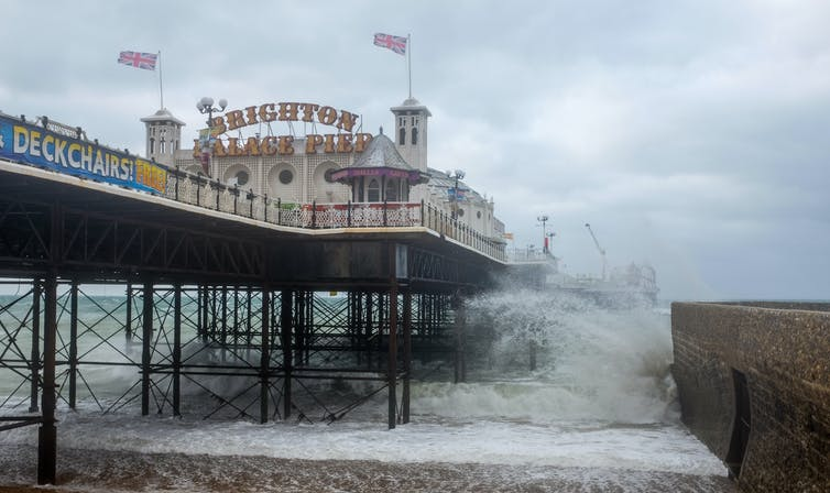 Waves crash against the UK's Brighton Pier in a storm.
