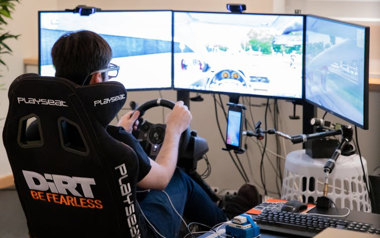 A person sits in a driving simulator