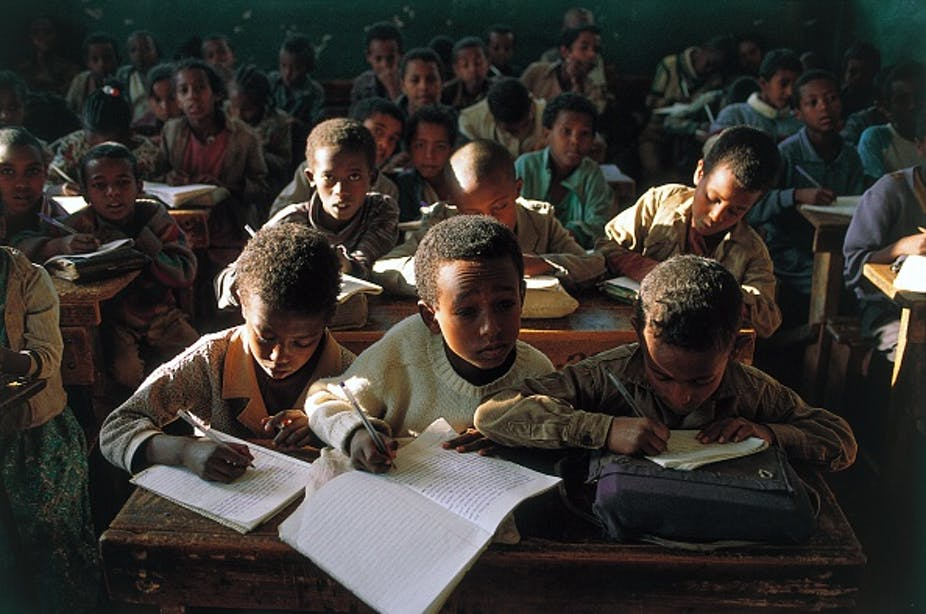 Children sitting at desks in a crowded classroom, poorly lit