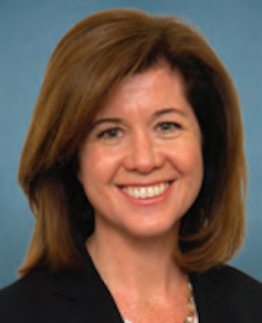 A brown-haired woman of middle age, smiling