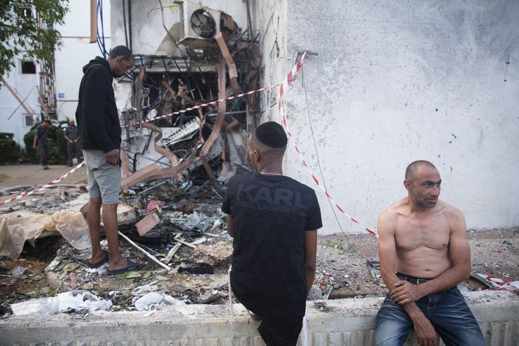Three people looking at rubble from a building destroyed by a rocket attack.