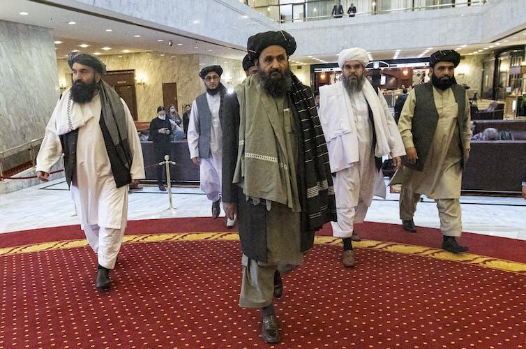 Taliban leaders walk though a lobby.