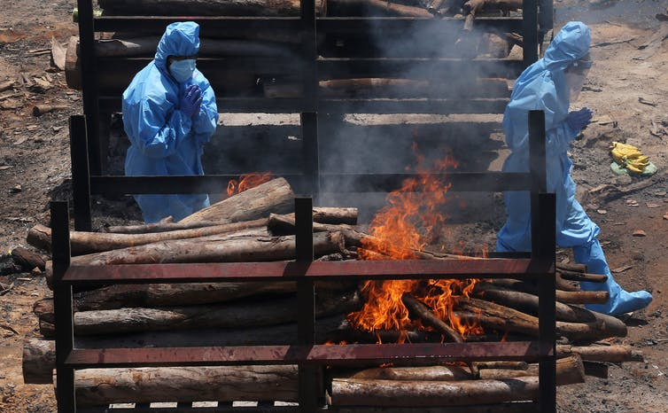 Two funeral workers in full PPE walk past a pyre in India.