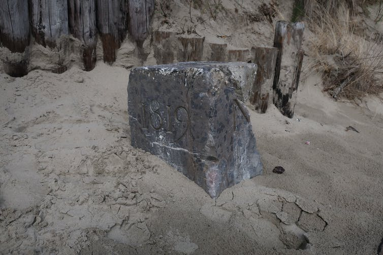 A border stone half buried in sand.