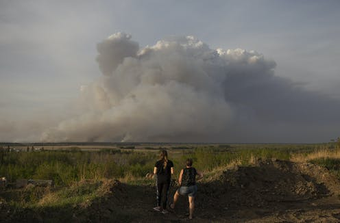 Two people watch a large cloud of smoke rising over fields.
