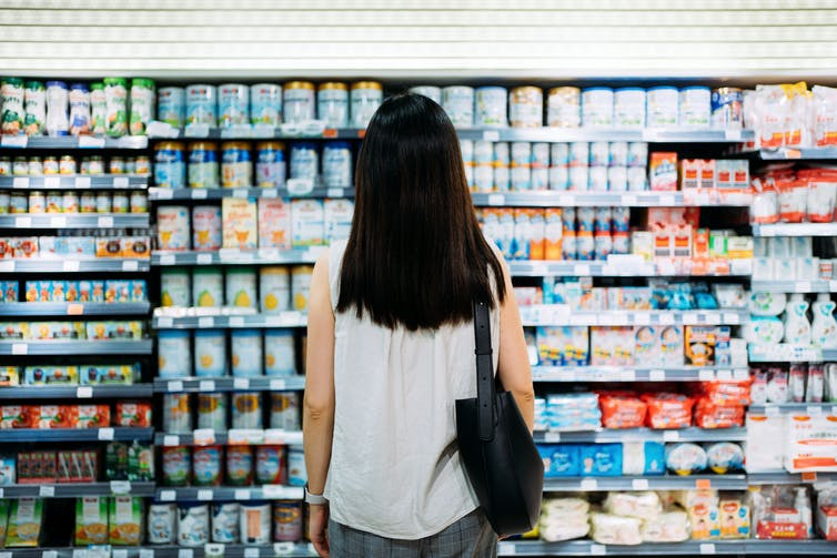 A woman stands in front of a massive grocery store display of infant formula.