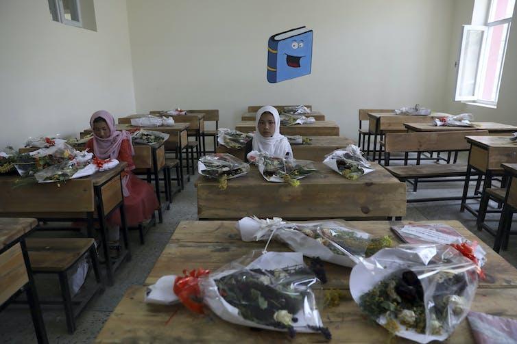 Schoolgirls sit inside a classroom with bouquets of flowers on empty desks