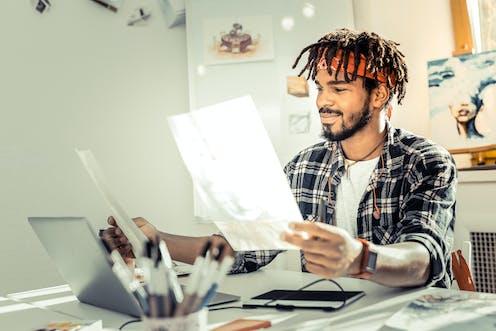 Man sat at desk looks at artwork