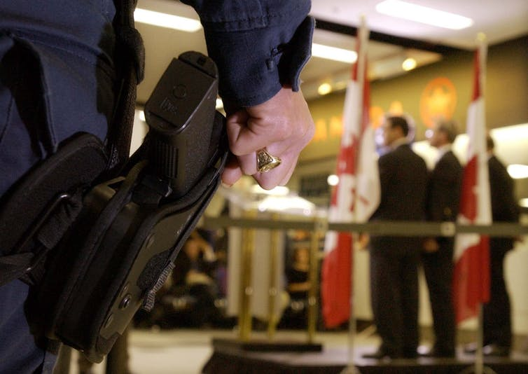 A police officer's hand rests on his gun as politicians speak in the background.