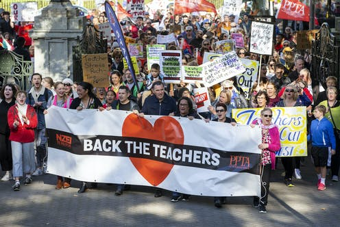 teachers protesting for more pay holding banners