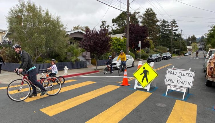 Residents ride bikes past a barrier directing traffic away from a local slow street.