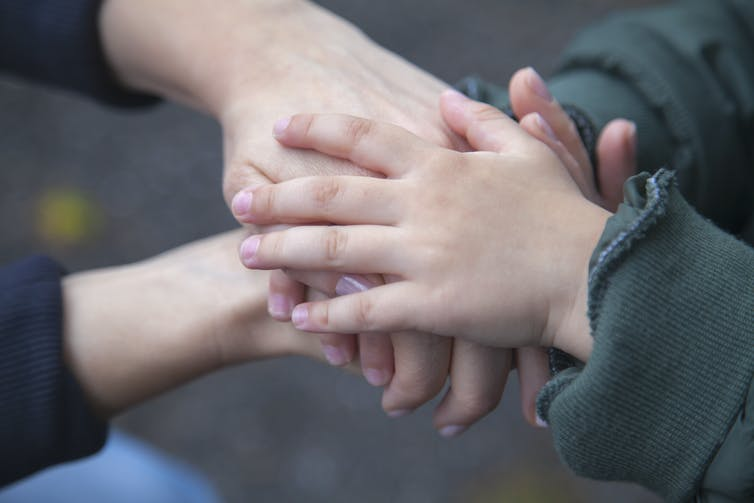 Mother and child place their hands atop each other's