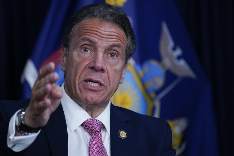 Andrew Cuomo in front of flag