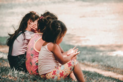 Three little girls sit side by side in a garden