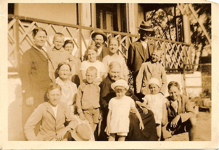 A sepia-toned photograph shows a group of men, women and children in older clothing outside a home