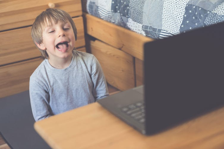 A young boy does a speech therapy session online in front of a laptop