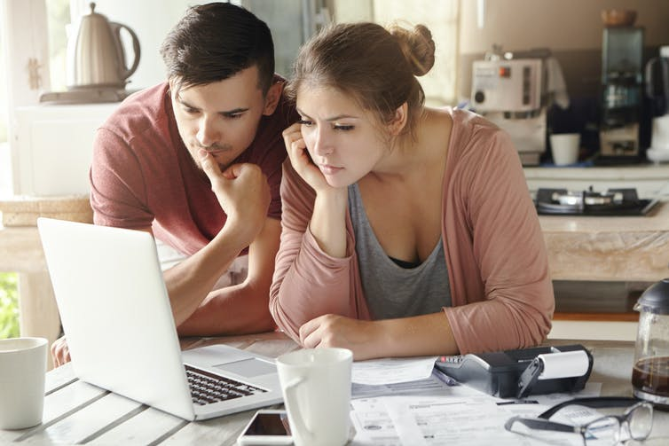 Serious man and woman sitting at kitchen table in front of open laptop computer, looking at screen