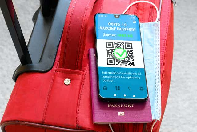 A phone showing a vaccine passport and a traditional passport on top of a travel bag