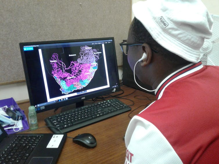 A person wearing a white hat and a red and white shirt, with white headphones, looks at a computer screen.