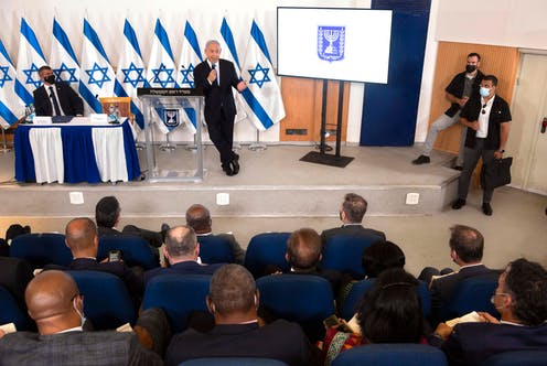 Israeli Prime Minister Benjamin Netanyahu, standing in front of multiple Israeli flags, giving a briefing to foreign diplomats from a military base in Tel Aviv.