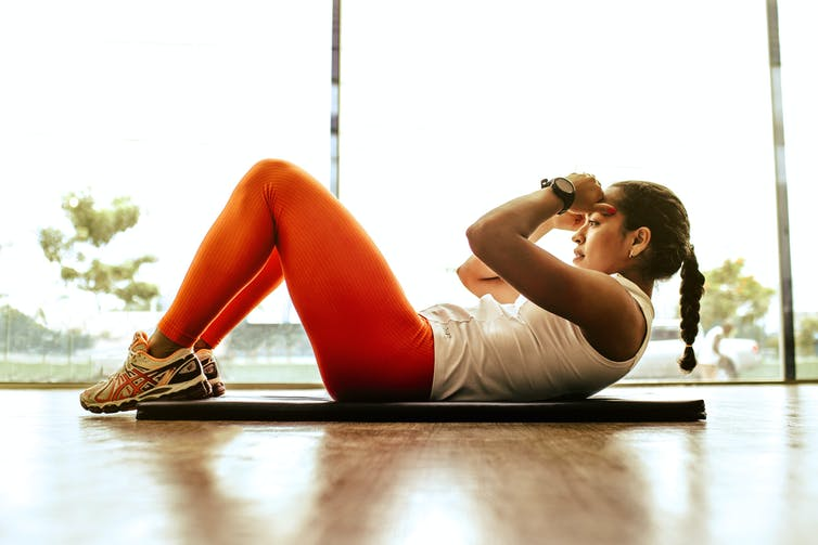 A woman in red leggings does crunches on an exercise mat