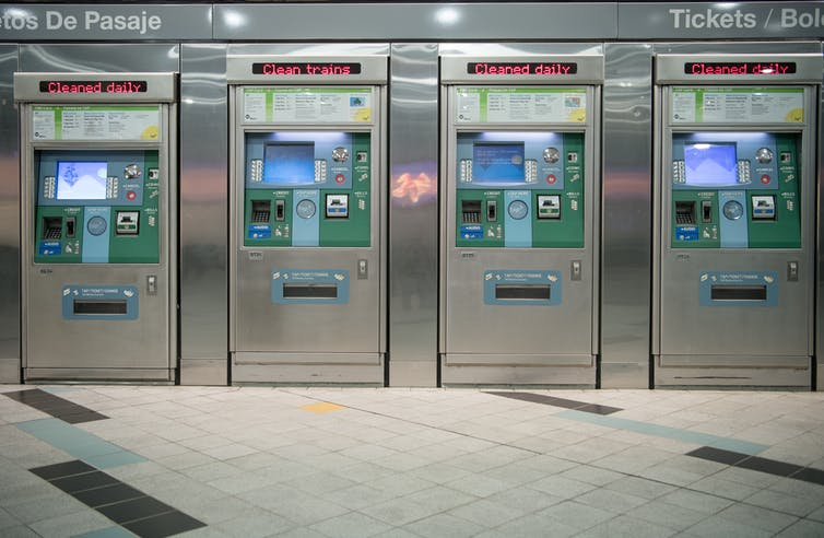 Four gleaming, clean and unused ticket-vending machines in a subway station