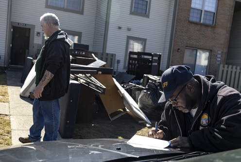 A man turns away from a pile of his belongings on a lawn, while a bailiff completes paperwork