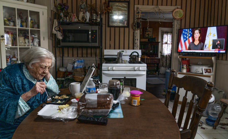 An elderly woman eats a meal by herself at her kitchen table.