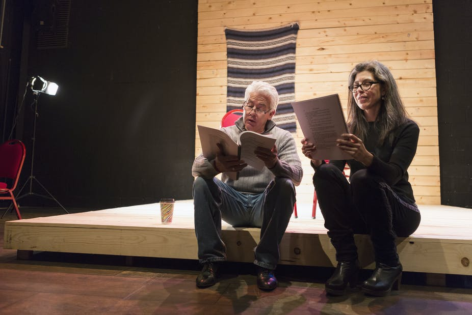Hispanic man and woman reading scripts on theater stage.