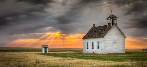 A old church building in a field. Above sunlight peeks through grey clouds.