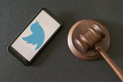A phone showing the Twitter logo next to a judge's hammer