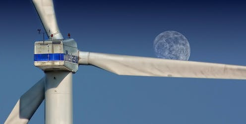 The blades of a wind turbine are seen against a blue sky with a full moon