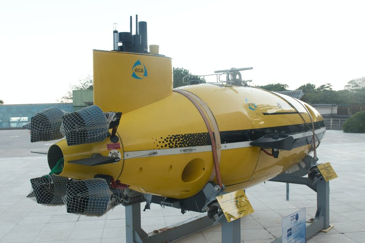 A yellow submarine vehicle is mounted on a stand on land