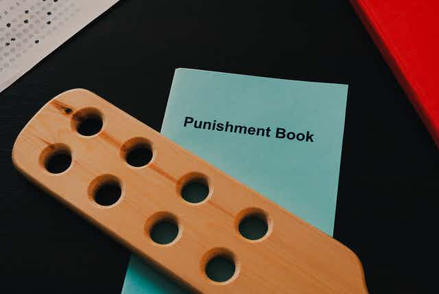 A wooden paddle and a book titled 'Punishment Book' sit on a desk.