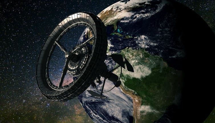 A circular space station in orbit in front of Earth.