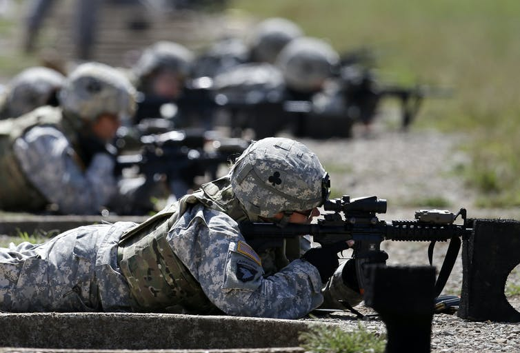 Soldiers lie on the ground firing guns