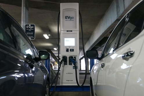 Two electric cars charging in a train station garage.