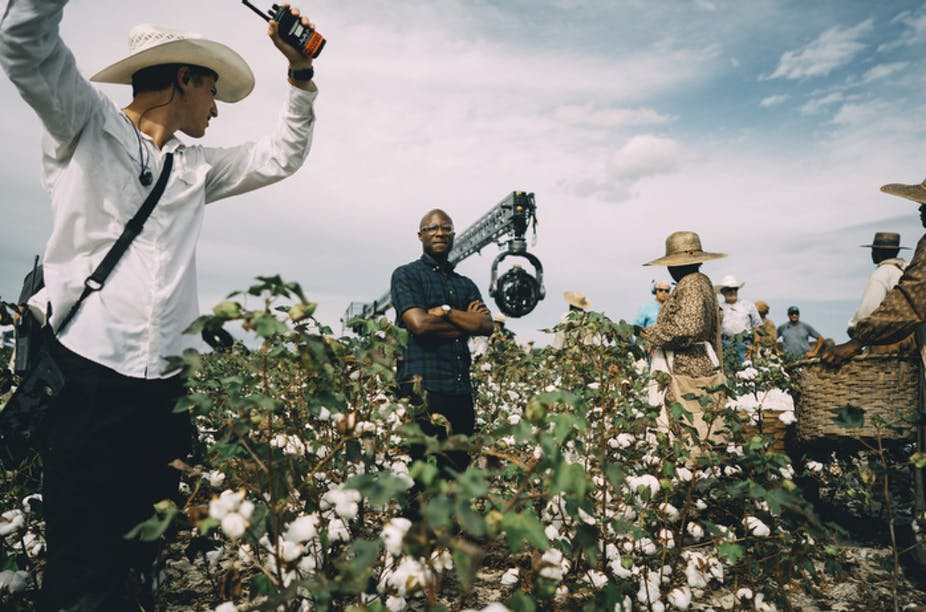 Barry Jenkins stands, arms folded, in a cotton field, surrounded by crew and cast.