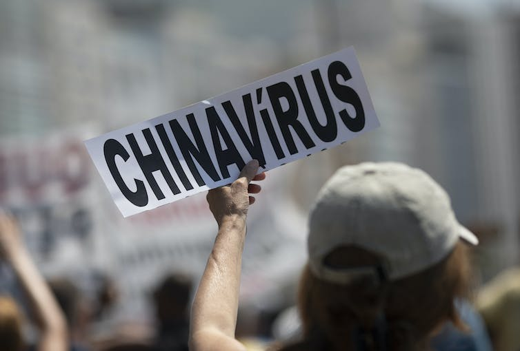 Person holds sign that reads 'CHINAVIRUS'