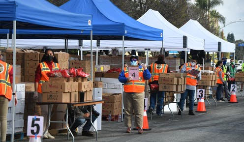 A food bank in Los Angles, distributing items to people in need outside a library.