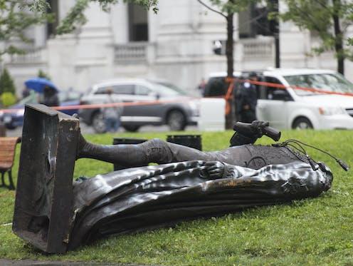 A toppled statue lies on grass
