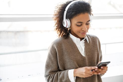 Une jeune femme devant une fenêtre écoute un balado sur son téléphone.