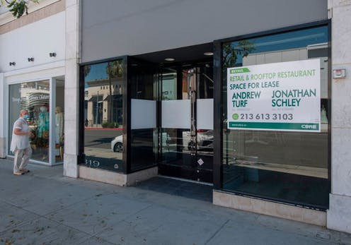 People walk past empty stores and restaurants closed due to impact of Covid-19 in Beverly Hills, California