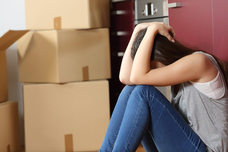 Teen or young woman with head in hands next to pile of cardboard moving boxes